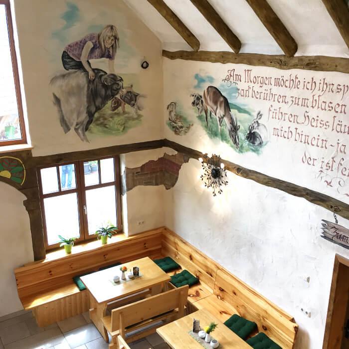 Brockenbauer Lokal Restaurant Innenansicht von Oben auf Sitzgruppe und Wand Spruch